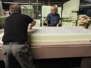 二人の熟練工が木枠にマットを詰める