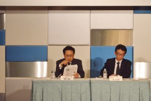 記者会見する芳賀信享社長(左)